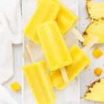 Overhead view of mango passion fruit popsicles stacked on a plate of ice