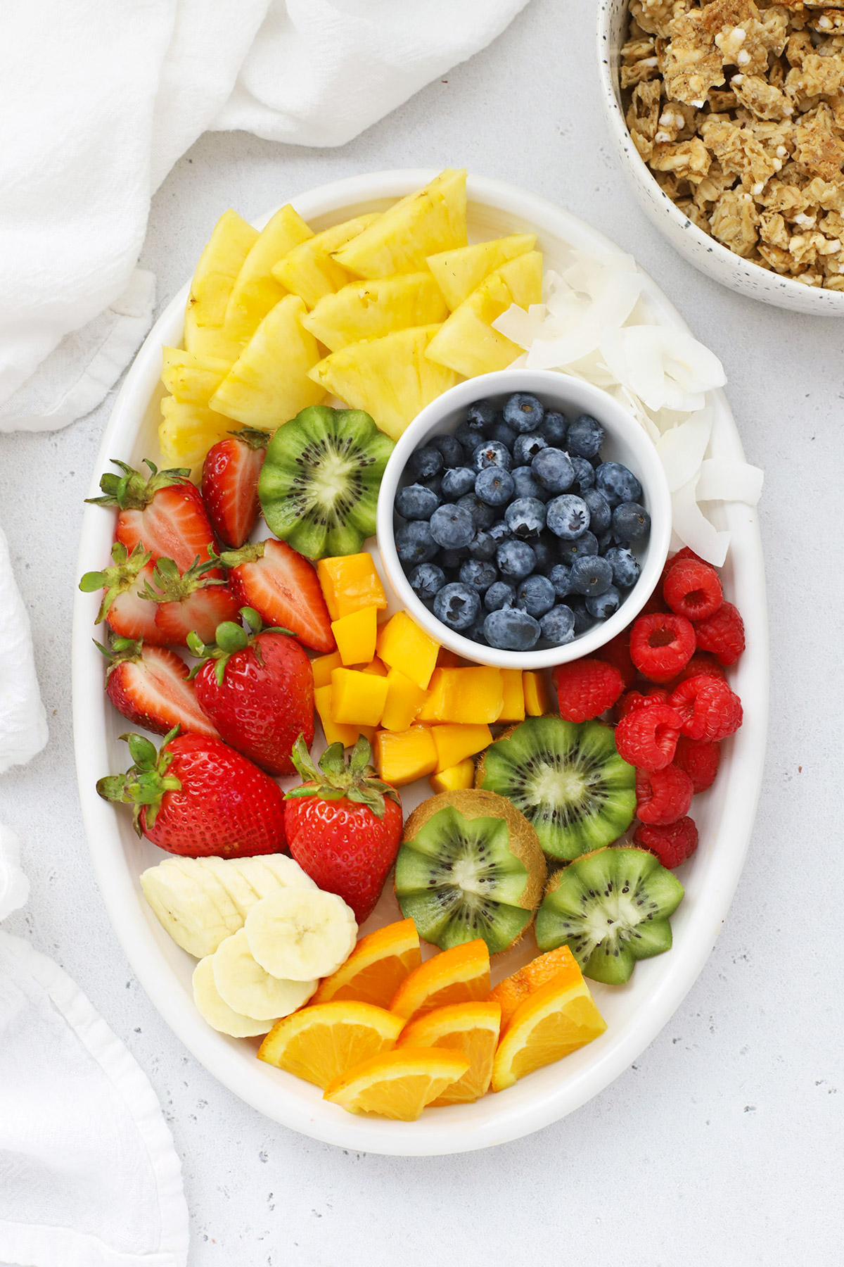 Overhead view of a fruit plate with colorful fruit, ready to top pineapple acai bowls