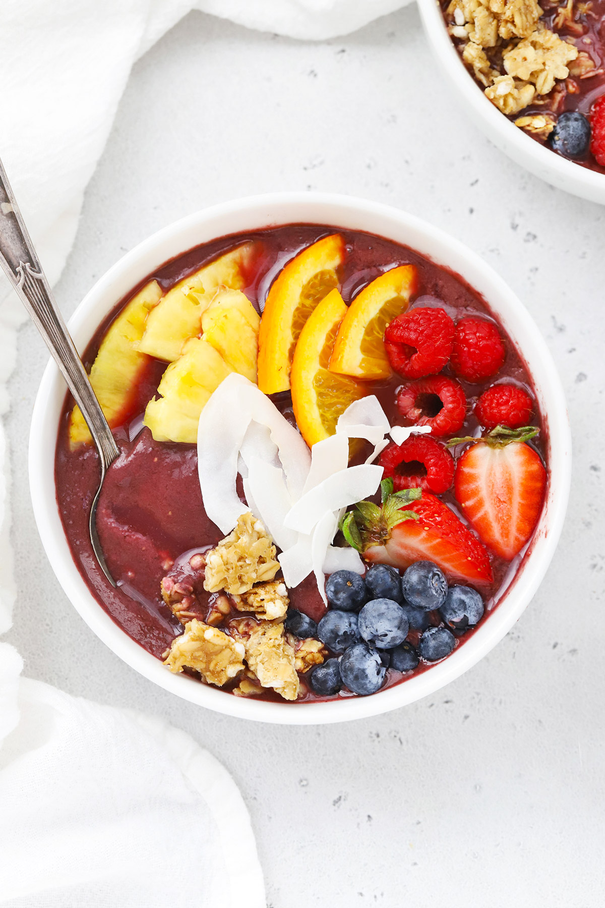 Overhead view of a pineapple acai bowl with fresh berries, pineapple, orange slices, shaved coconut, granola, mango on a white background