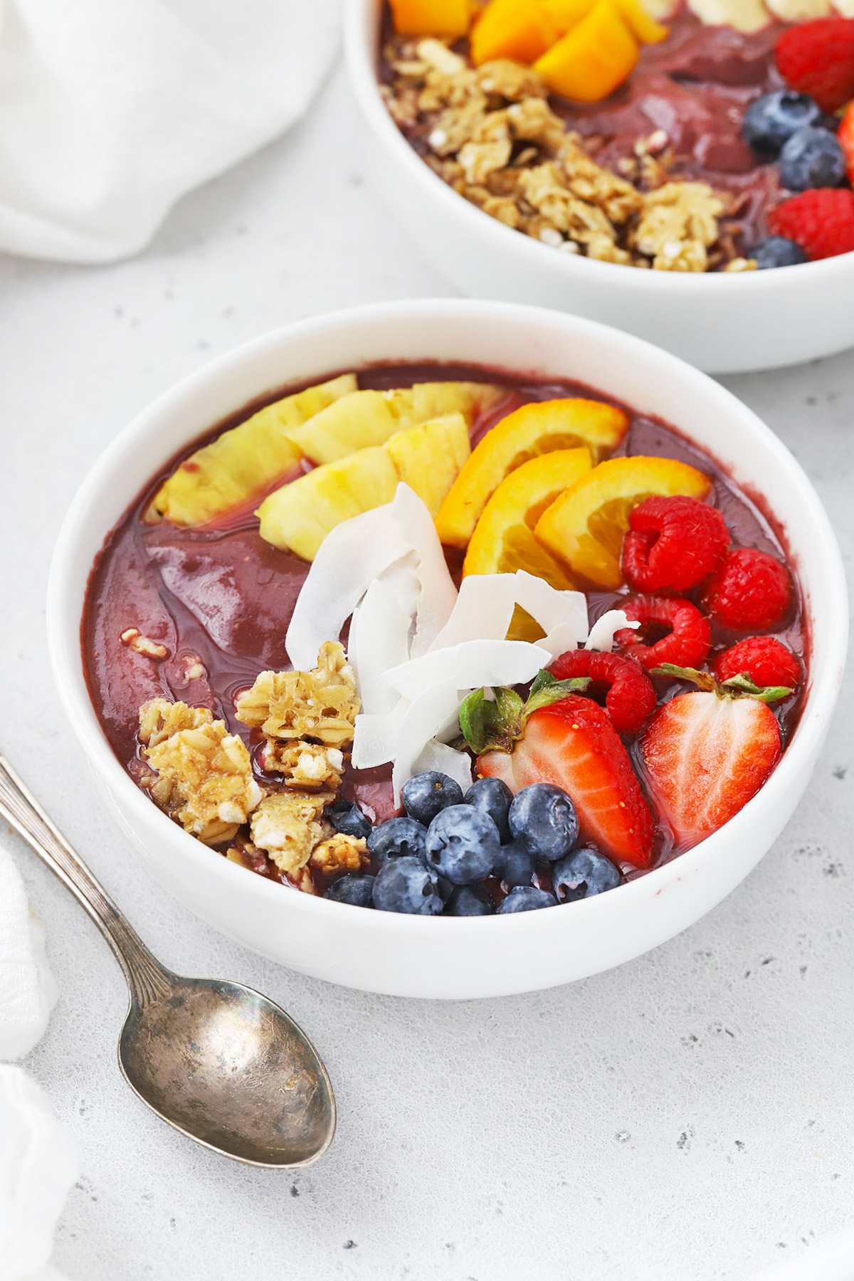 Front view of a pineapple acai bowl with fresh berries, pineapple, orange slices, shaved coconut, granola, mango on a white background