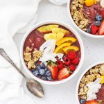 Overhead view of three pineapple acai bowls topped with fresh fruit and granola on a white background