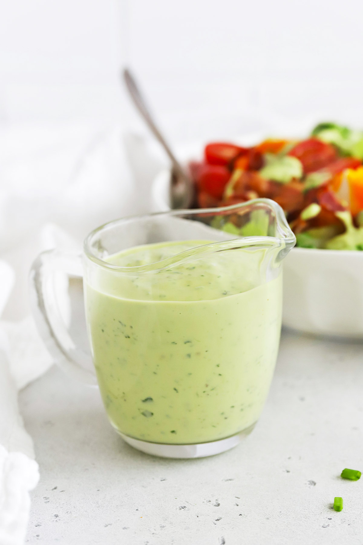 Front view of avocado green goddess dressing in front of a salmon cobb salad