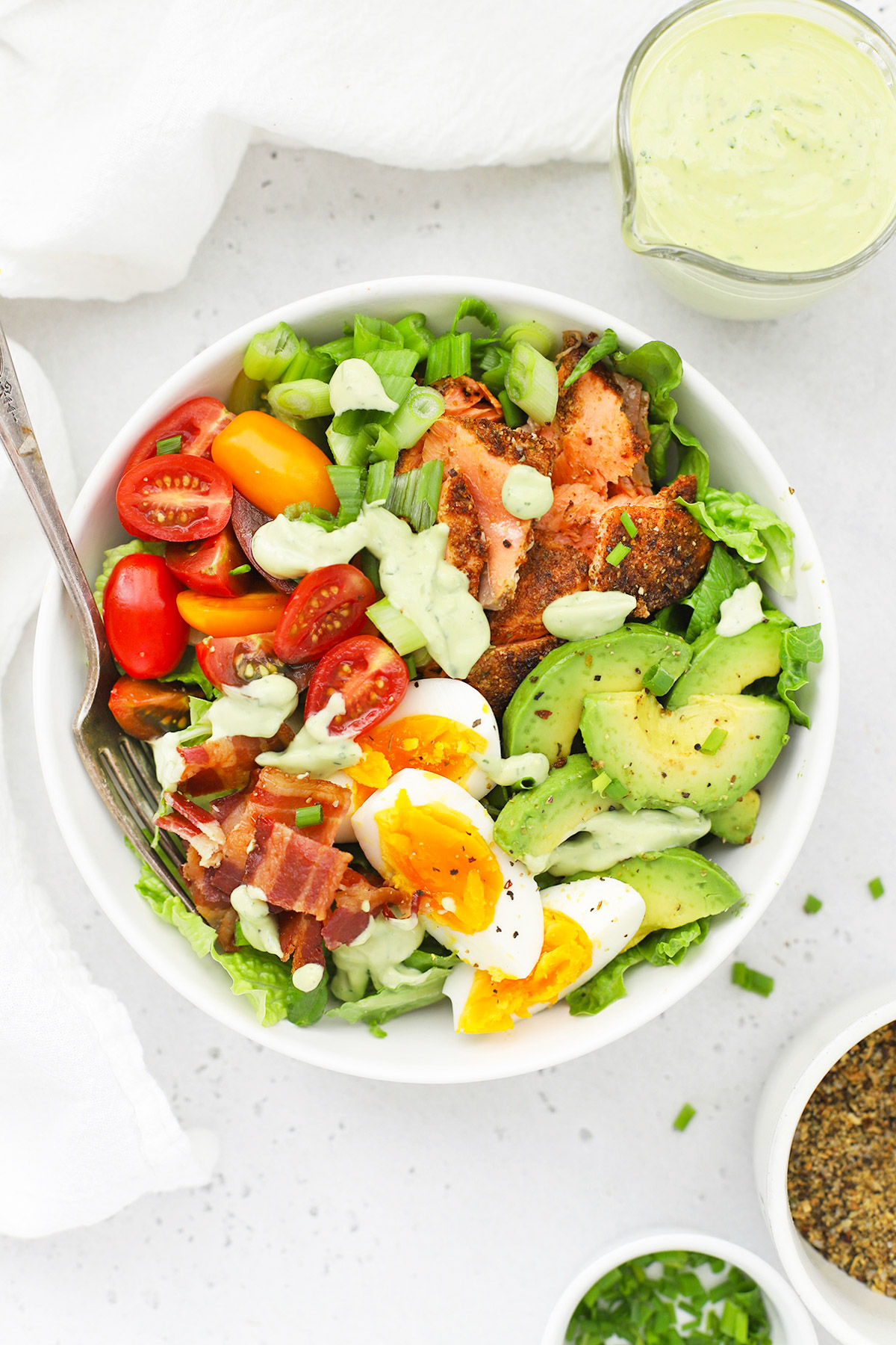 Overhead view of a blackened salmon cobb salad on a white background with avocado green goddess dressing on the side