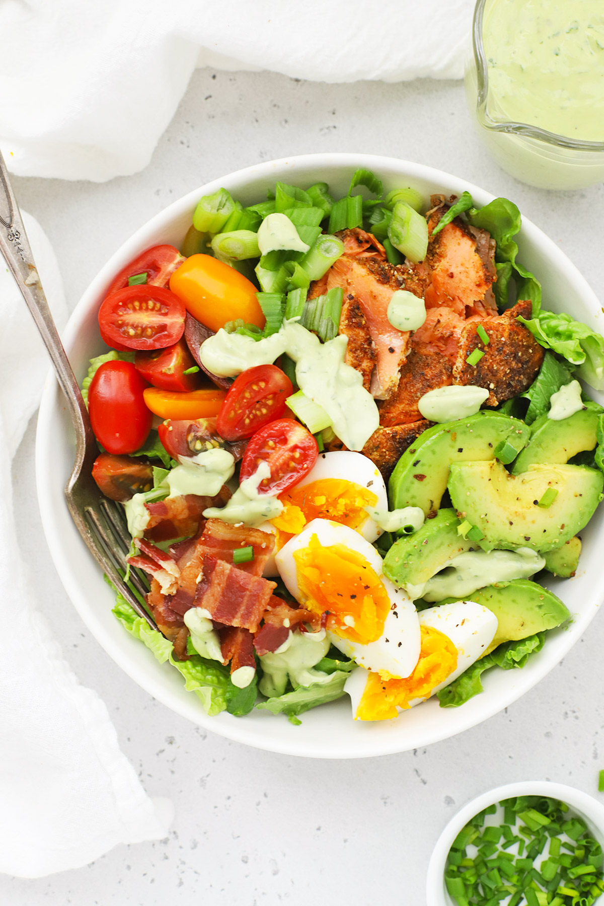 Close up overhead view of a blackened salmon cobb salad on a white background with avocado green goddess dressing on the side