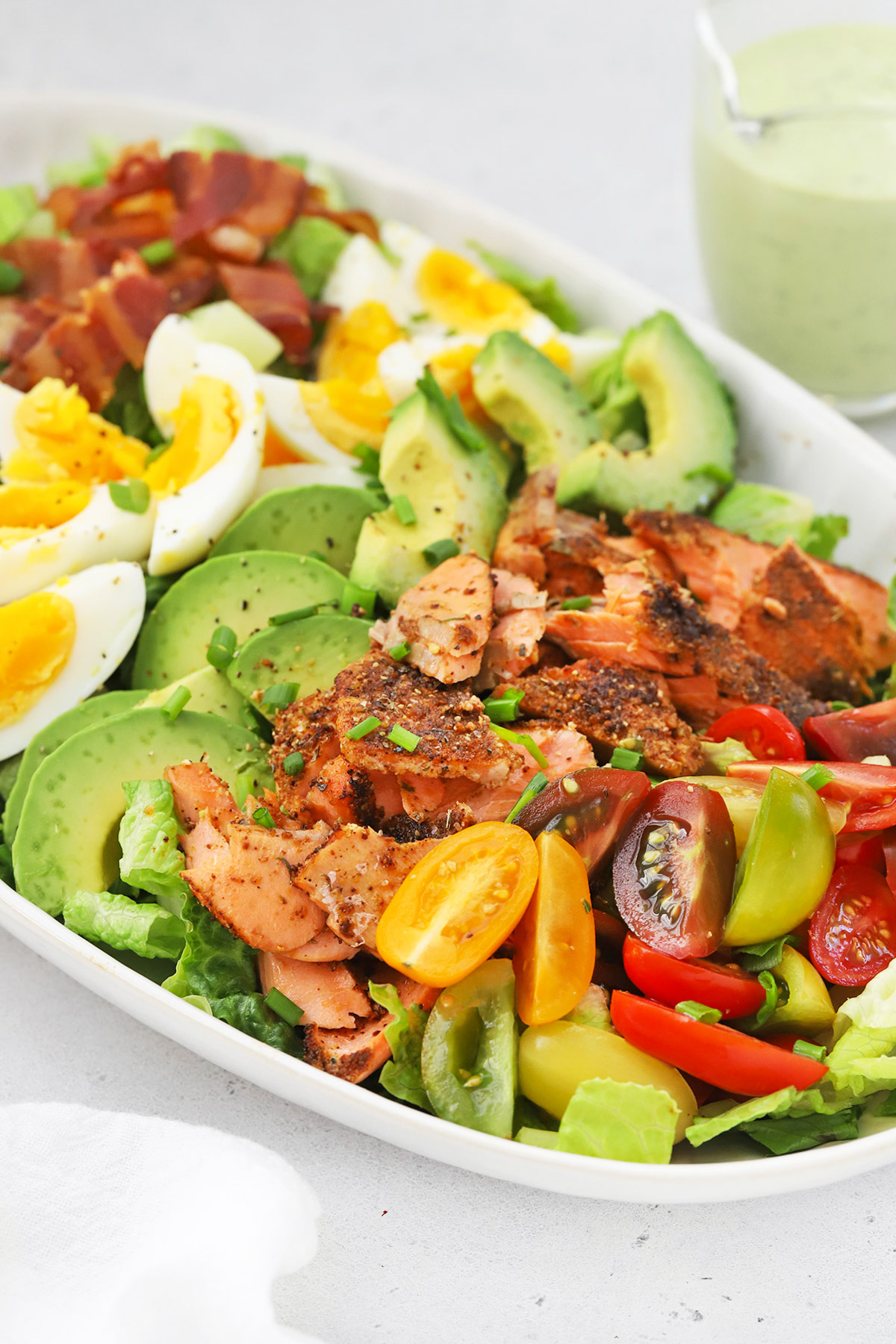Front view of a big platter of blackened salmon cobb salad with colorful ingredients arranged in rows.