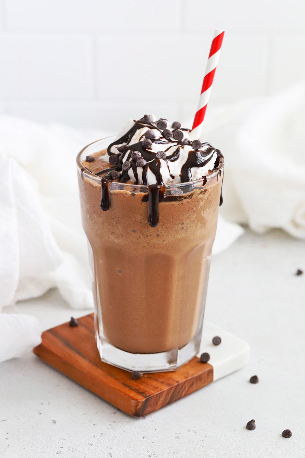 Front view of a glass of vegan frozen hot chocolate topped with coconut whipped cream and chocolate chips