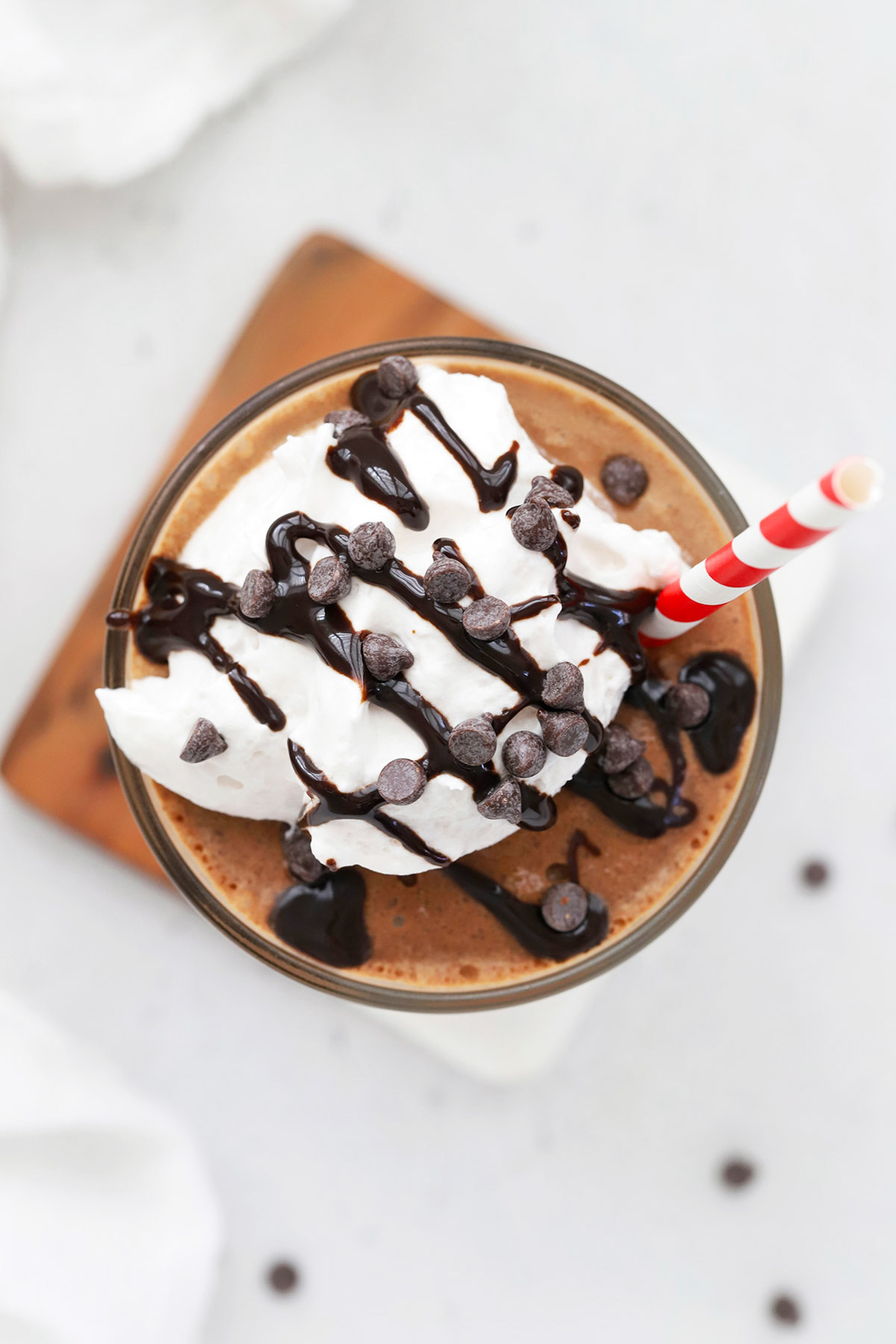 Overhead view of a glass of vegan frozen hot chocolate topped with coconut whipped cream and chocolate chips
