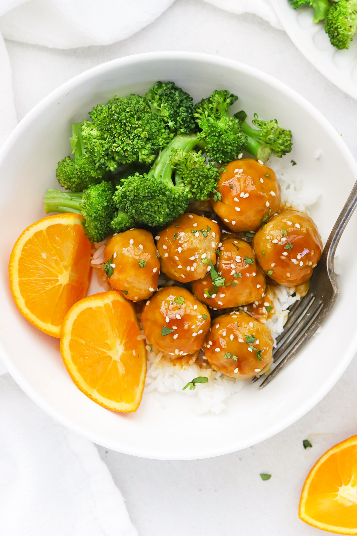 Overhead view of healthy orange chicken meatballs with rice and steamed broccoli