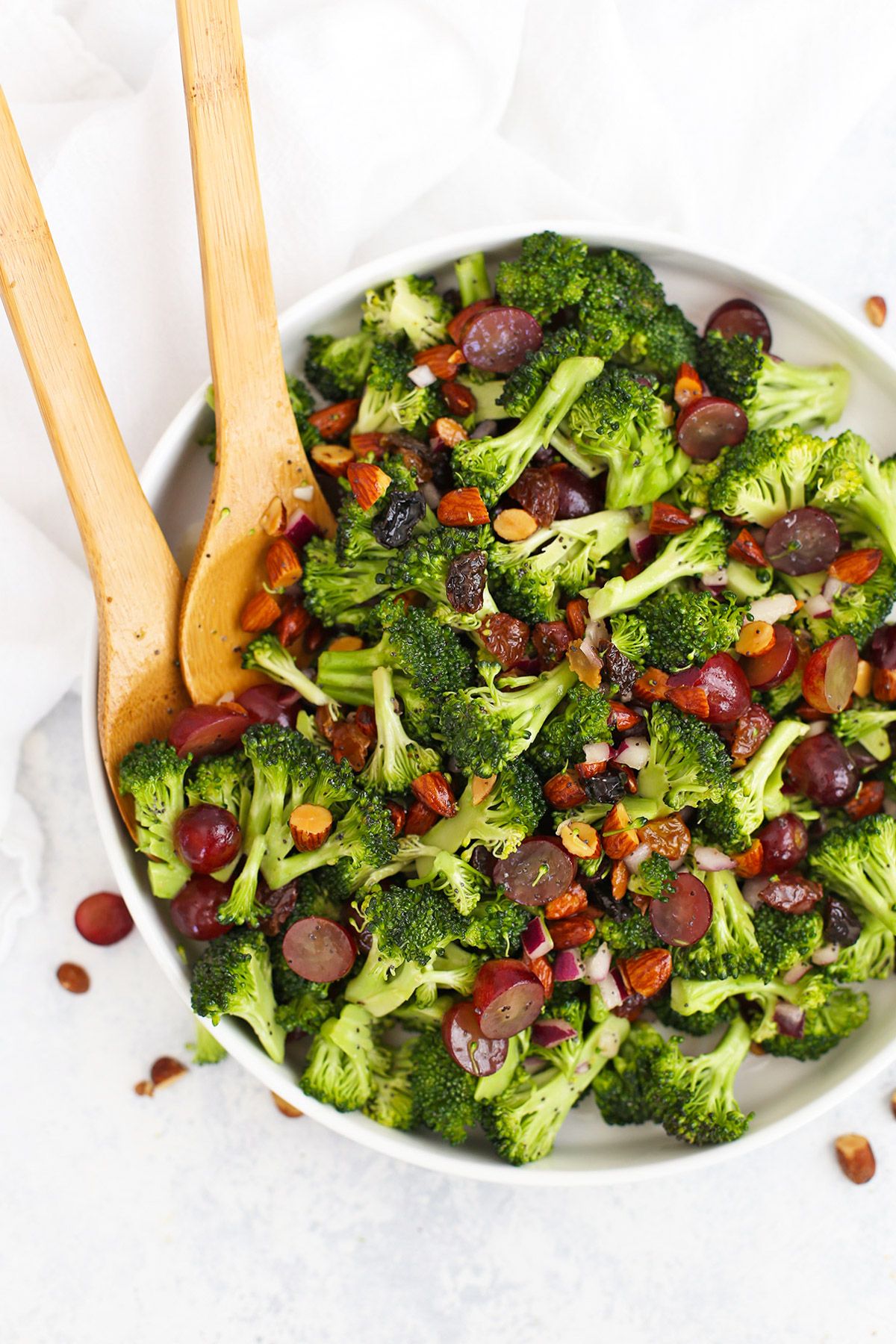 Overhead view of a bowl of vegan broccoli salad with poppy seed dressing, grapes, and smoked almonds