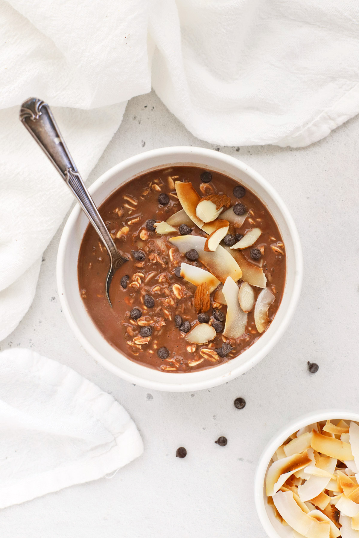 Overhead view of a bowl of almond joy overnight oats topped with chocolate and coconut.