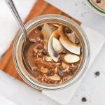 Overhead view of a jar of almond joy overnight oats topped with chocolate and coconut.