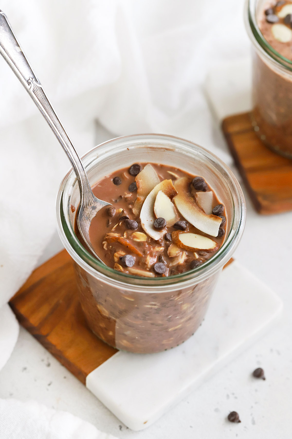 Front view of a jar of almond joy overnight oats topped with chocolate and coconut.