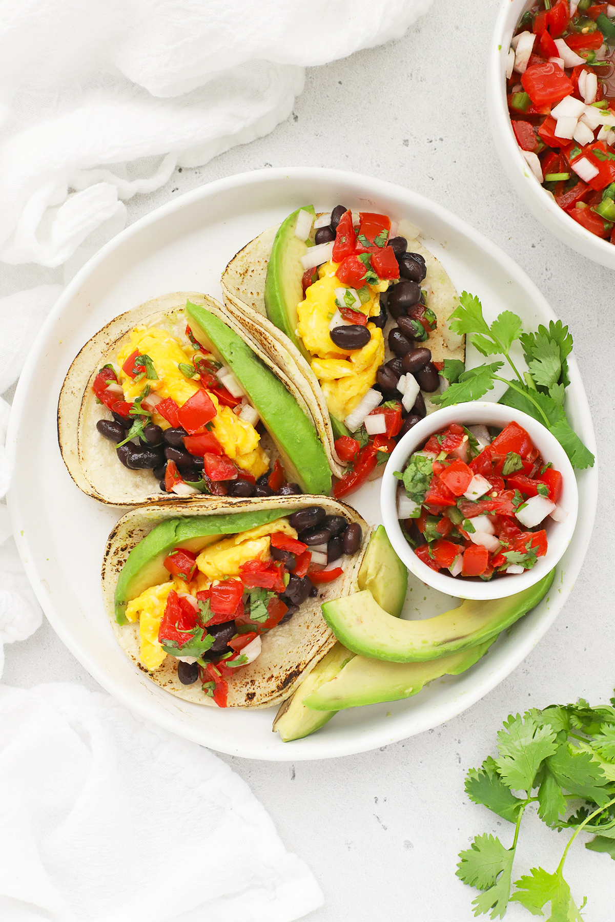 Overhead view of a platter of three healthy vegetarian breakfast tacos