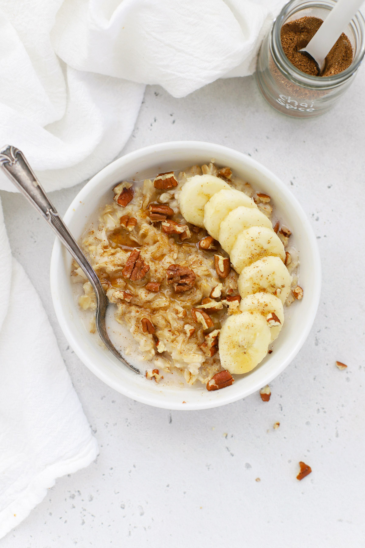 Overhead view of chai spice oatmeal with sliced bananas and toasted pecans
