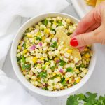 Overhead view of Chipotle Copycat fresh corn salsa with a tortilla chip dipped into it