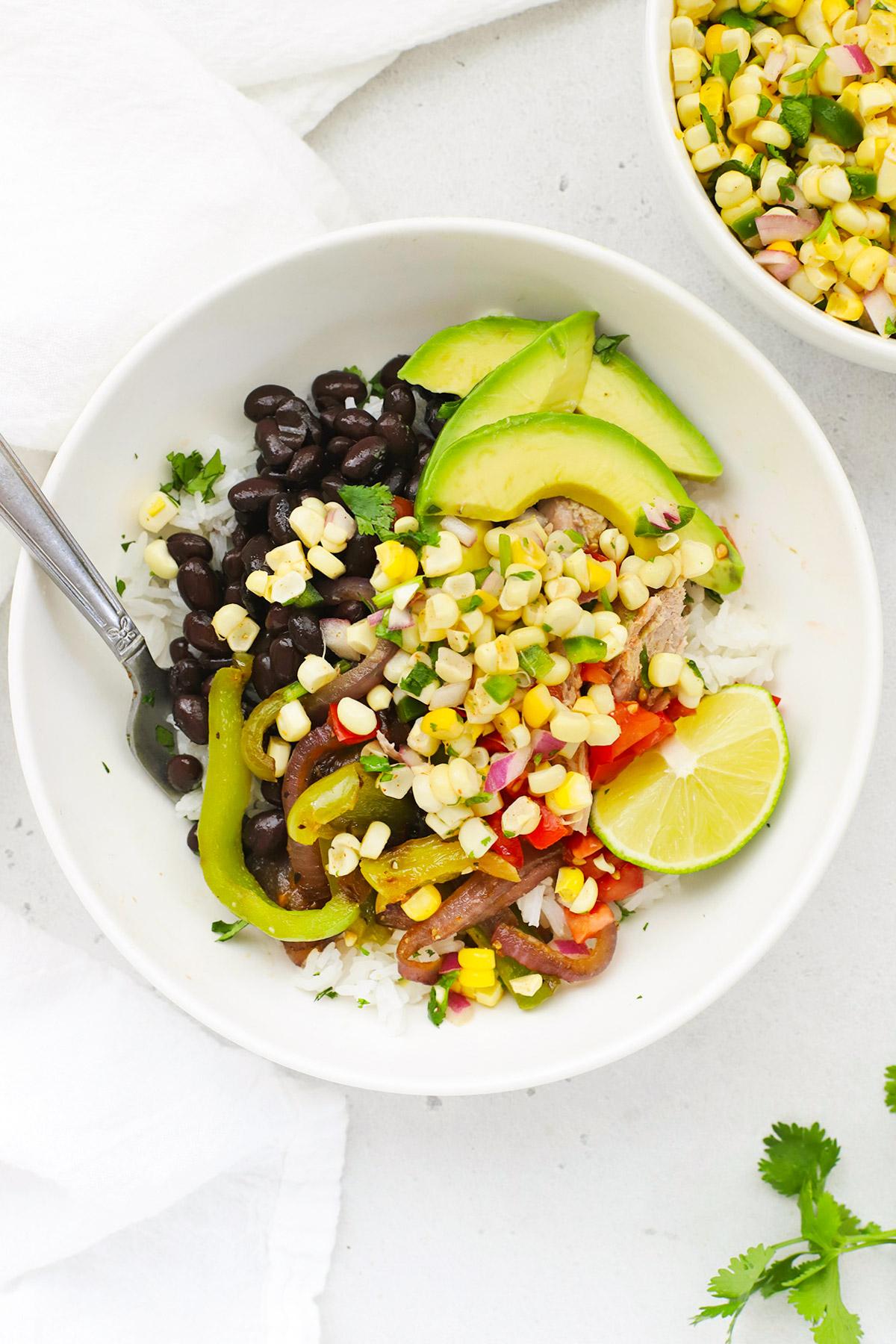 Overhead view of a burrito bowl with cilantro lime rice, fajita veggies, black beans, avocado, and chipotle copycat corn salsa