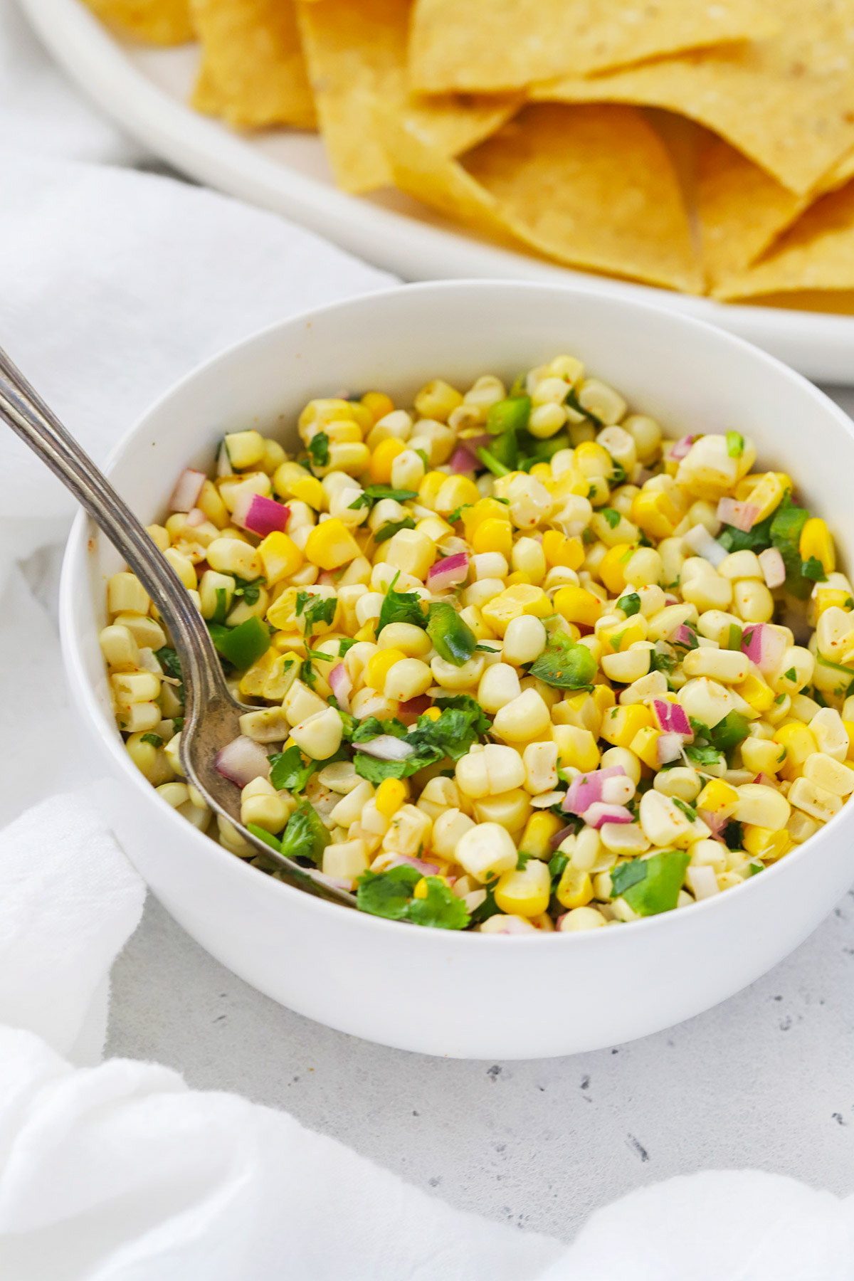 Front view of a bowl of fresh corn salsa with a platter of tortilla chips in the background