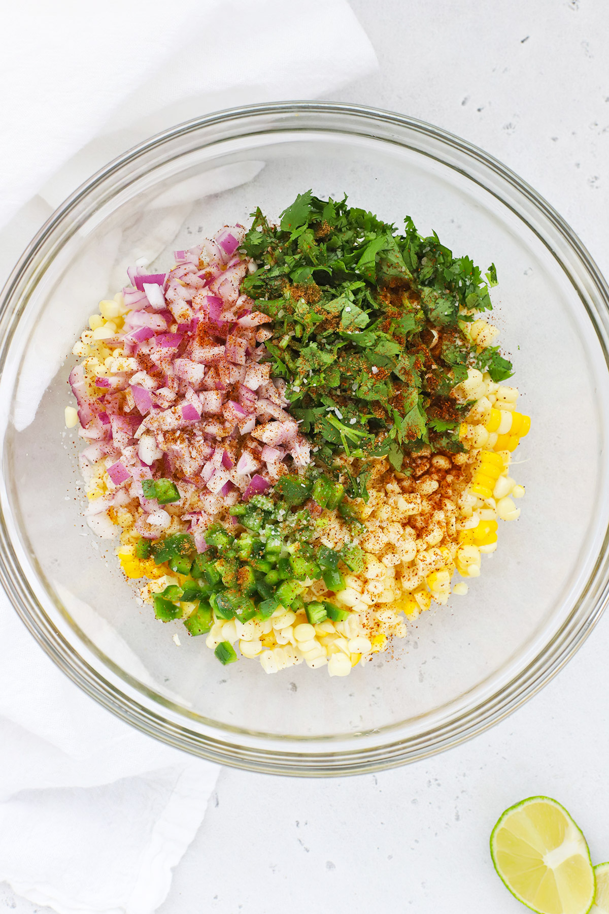 Overhead view of ingredients for fresh corn salsa in a mixing bowl ready to be stirred