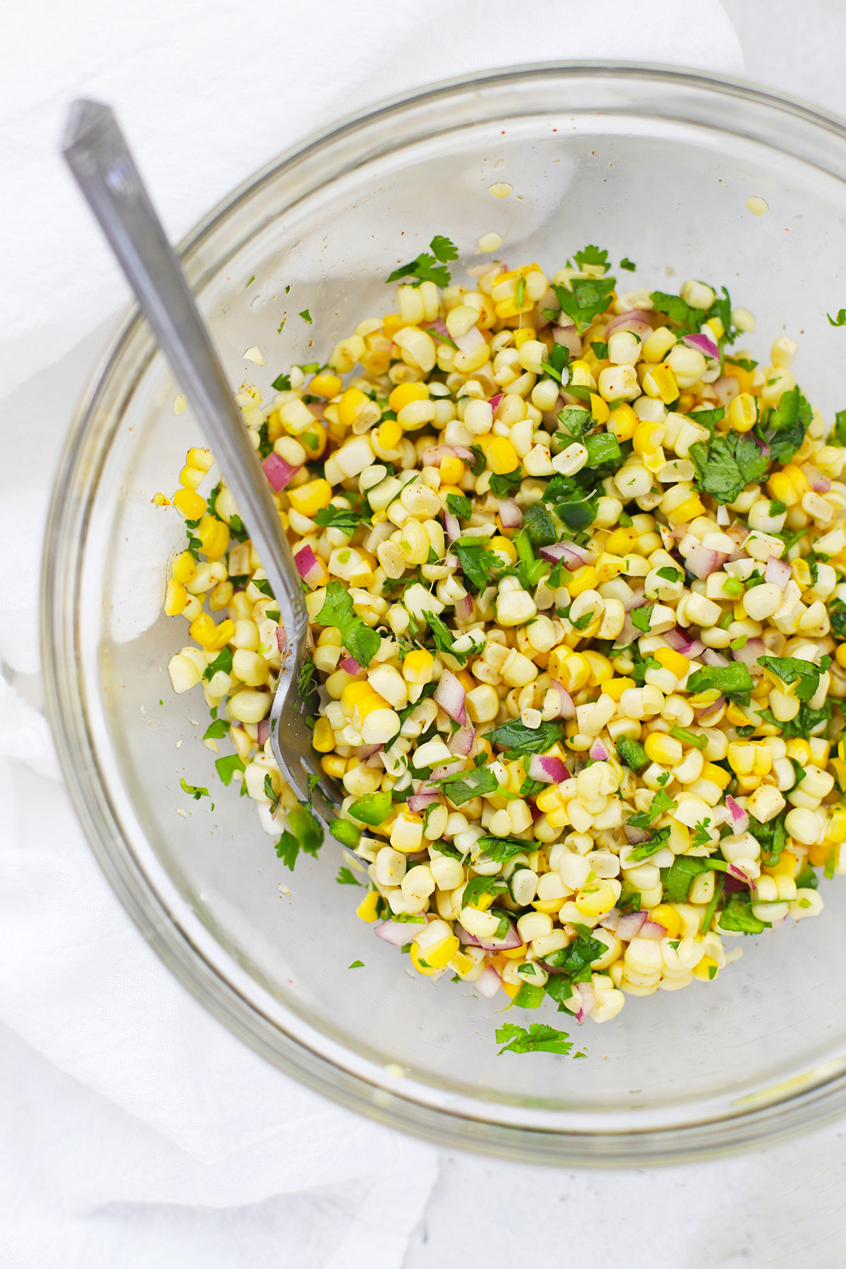 Overhead view of freshly mixed chipotle copycat corn salsa in a glass bowl