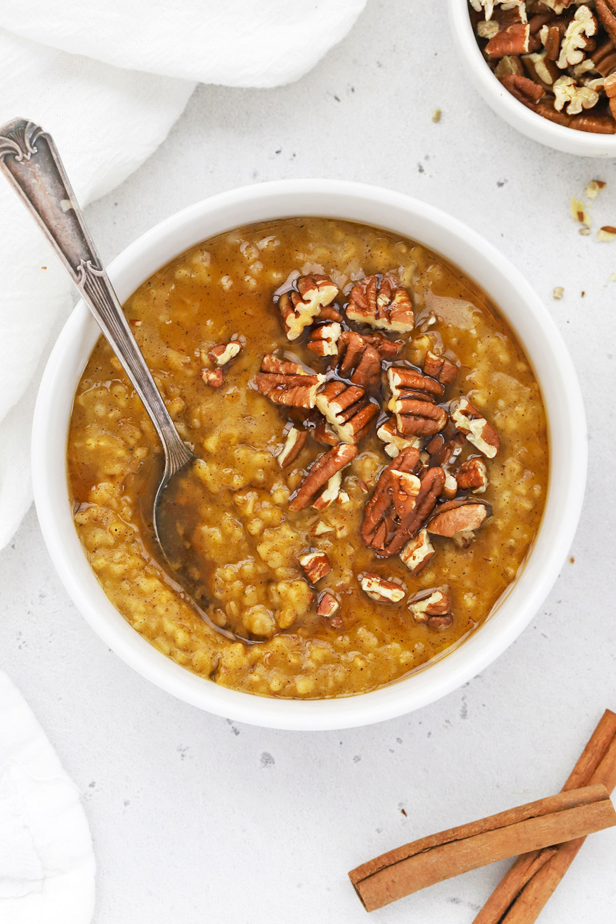 Close up overhead view of a bowl of Instant Pot Pumpkin Steel Cut Oats topped with maple syrup and pecans