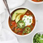 Overhead view of a bowl of vegetarian pumpkin chili topped with sour cream, jalapeño, and avocado