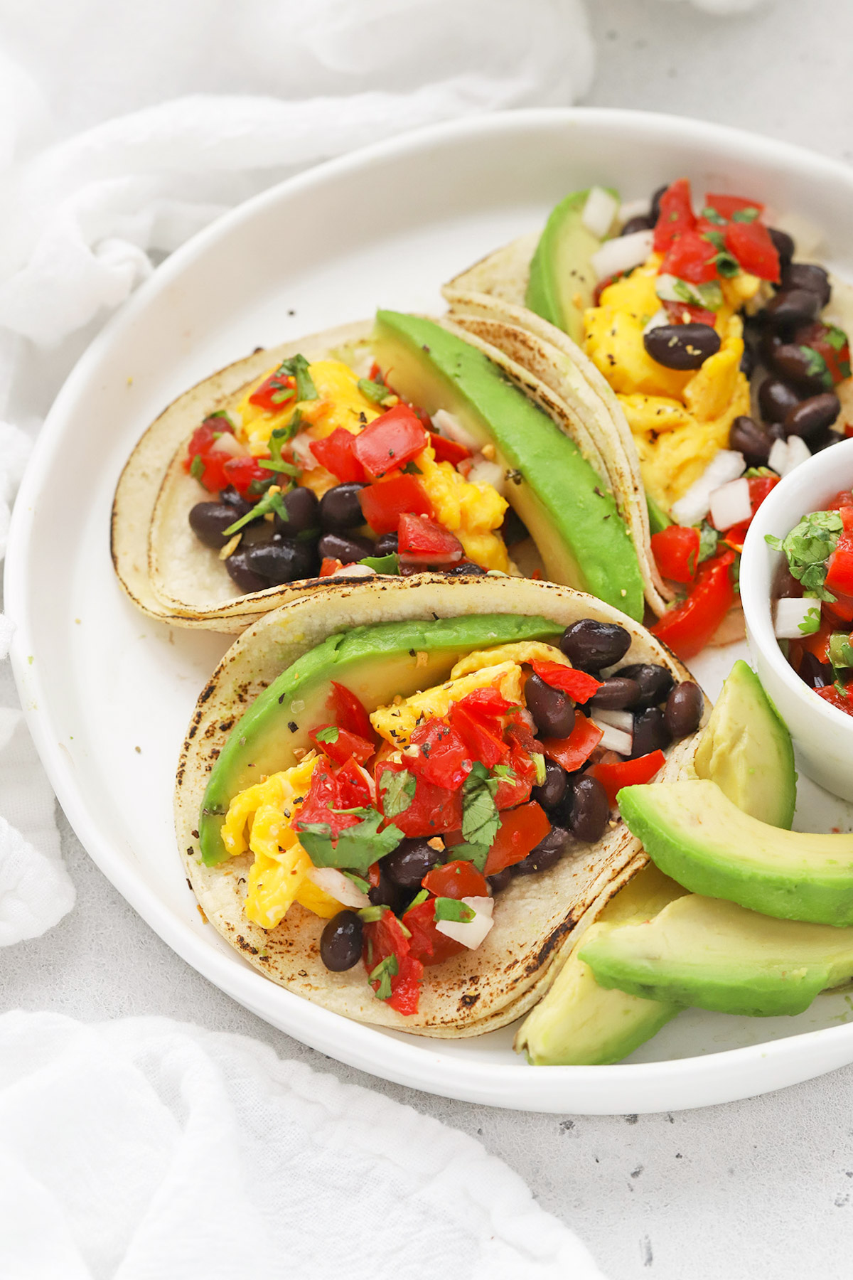Front view of a platter of three healthy vegetarian breakfast tacos