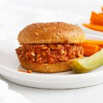 Front view of healthy chicken sloppy joes on gluten-free buns with a pickle wedge and carrot sticks