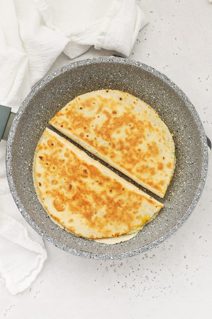 Overhead view of buffalo chicken quesadillas browning in a pan
