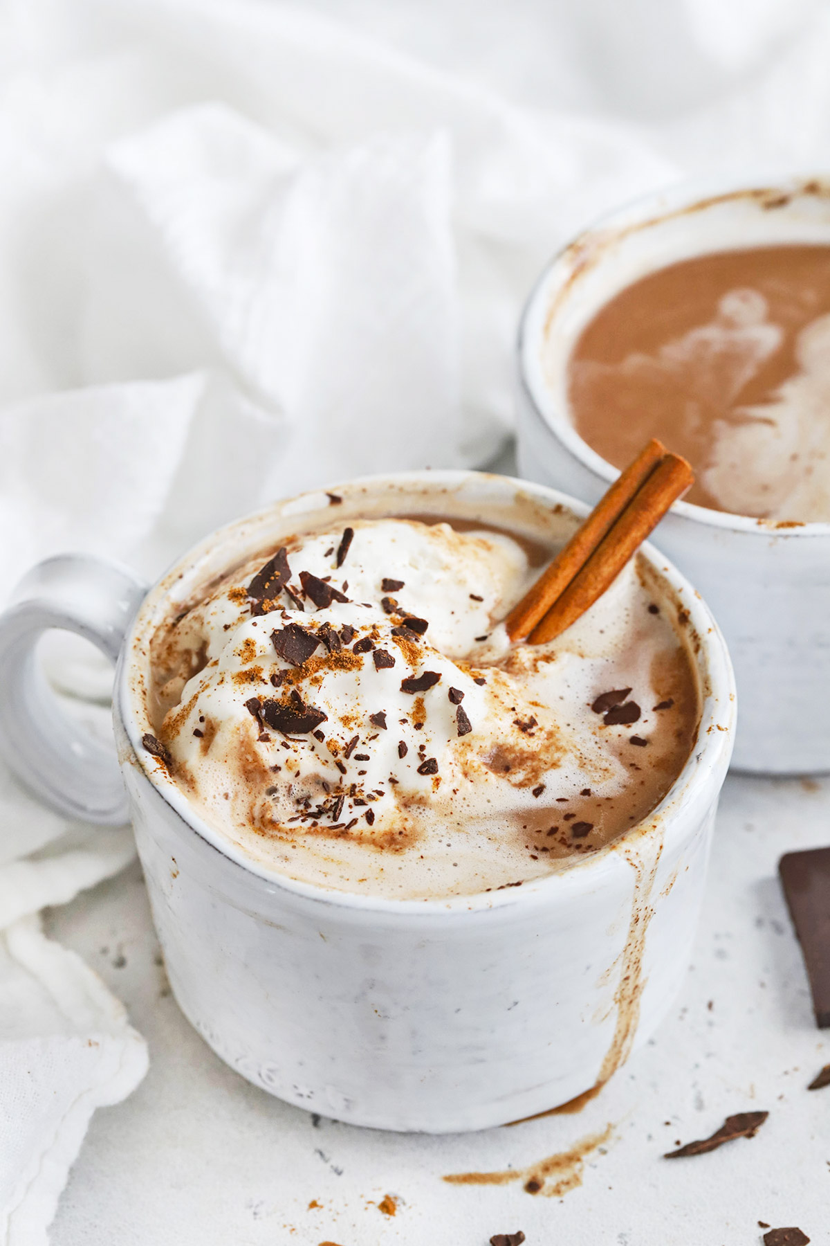 Front view of a steaming mug of dairy-free pumpkin spice hot chocolate topped with coconut whipped cream, shaved chocolate, and pumpkin spice
