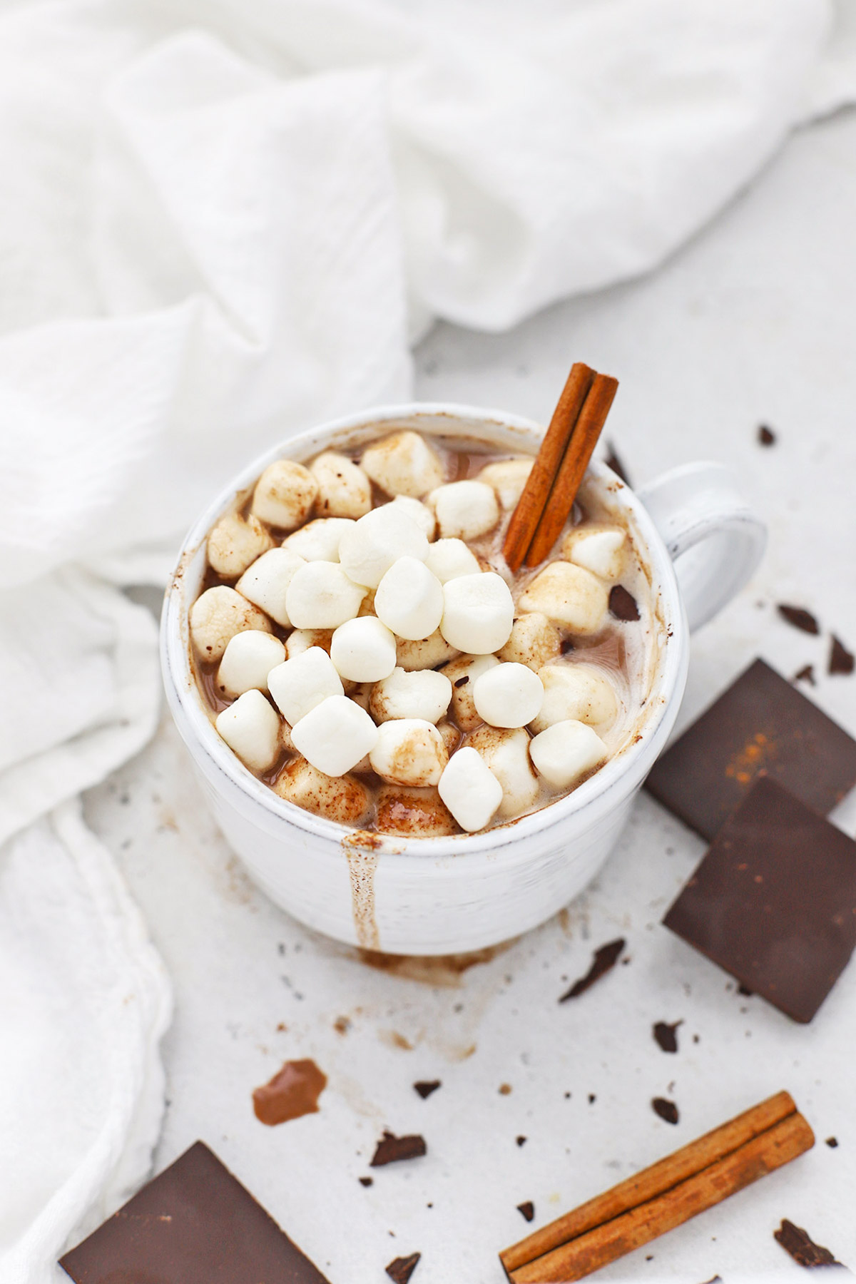Front view of dairy free pumpkin spice hot chocolate topped with vegan marshmallows and a cinnamon stick