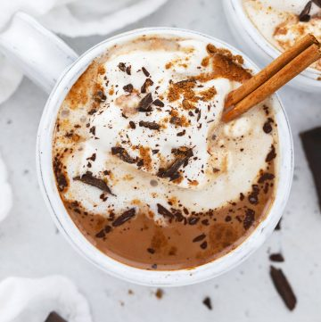 Overhead view of a steaming mug of dairy-free pumpkin spice hot chocolate topped with coconut whipped cream, shaved chocolate, and pumpkin spice