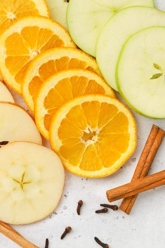Apple slices, orange slices, and cinnamon sticks for hot spiced cider