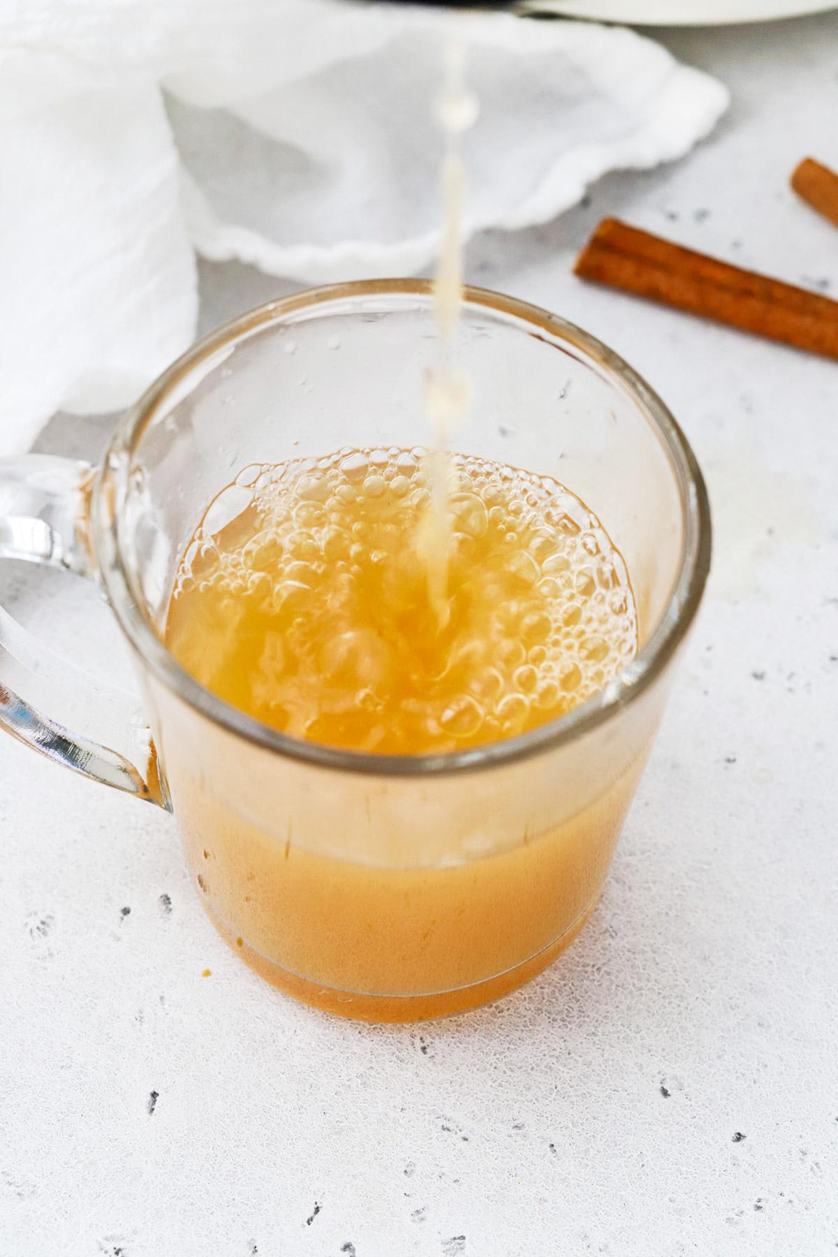 Pouring hot spiced cider into a glass mug