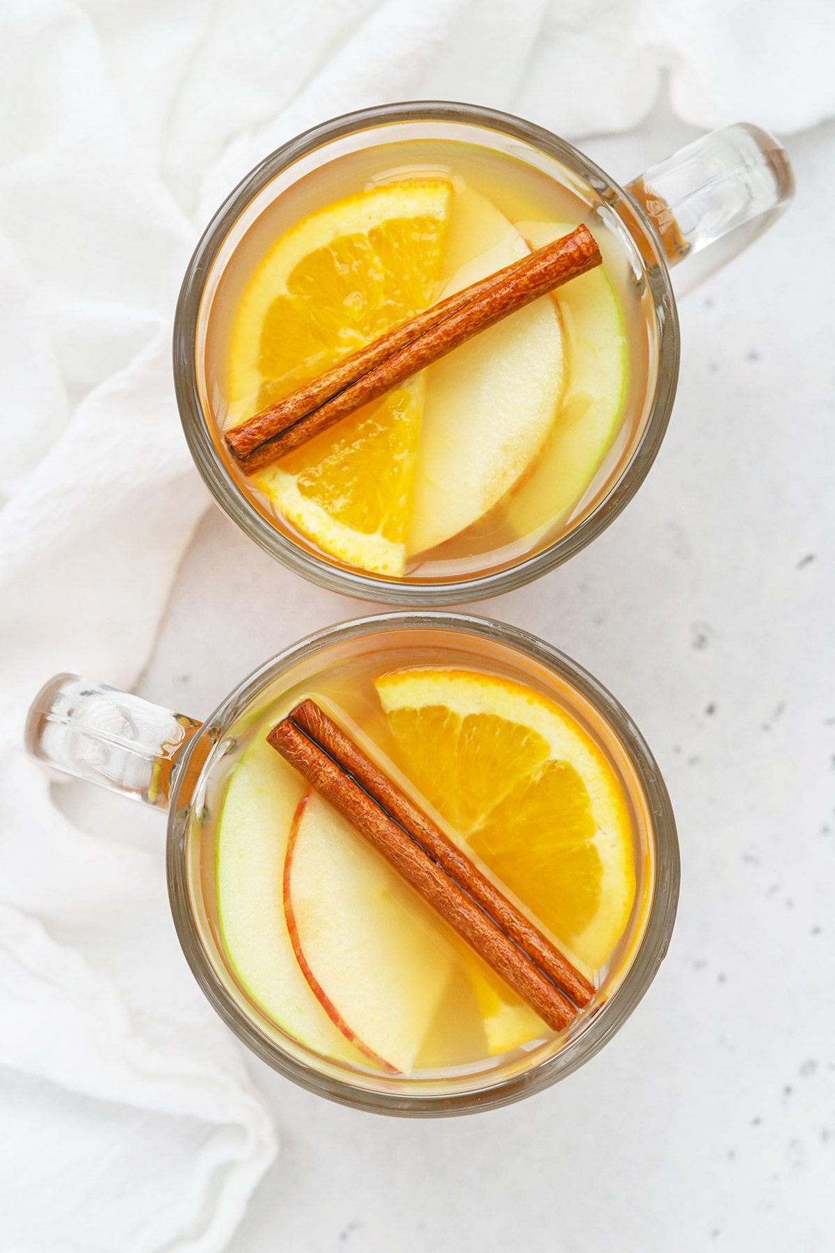 Overhead view of a glass mug of hot spiced cider garnished with apple slices, orange slices, and cinnamon sticks