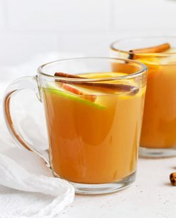 Front view of glass mugs of hot spiced cider garnished with apple slices, orange slices, and cinnamon sticks