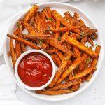 Overhead view of crispy baked sweet potato fries served with ketchup