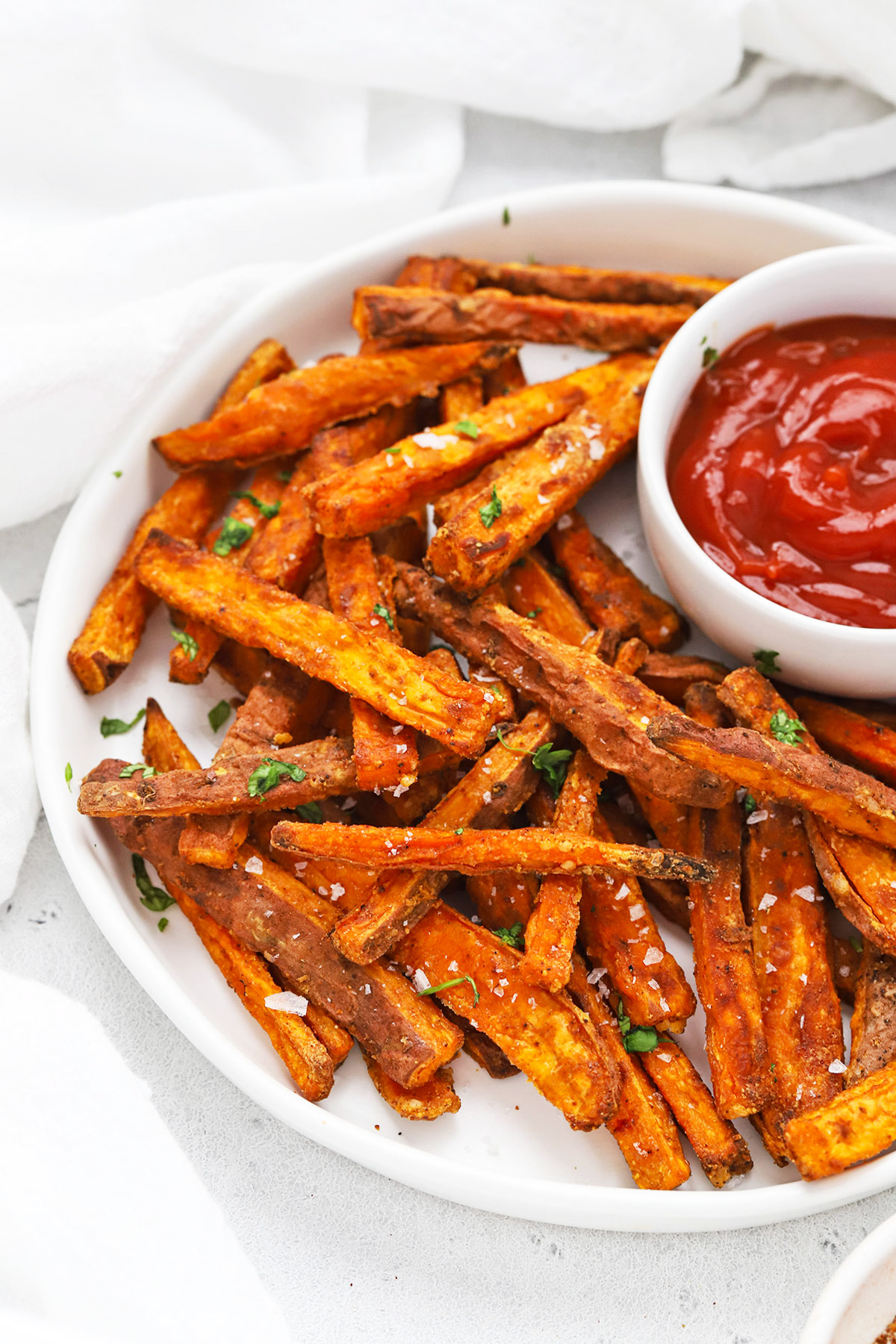 Front view of crispy baked sweet potato fries with ketchup on the side