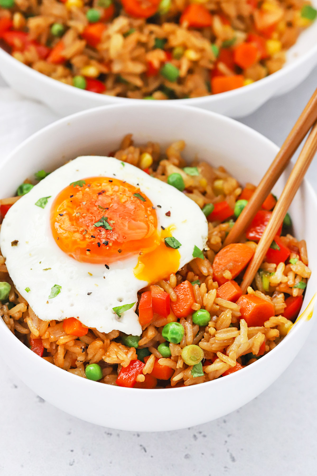 Front view of two bowls of healthy vegetarian fried rice topped with a sunny-side up egg