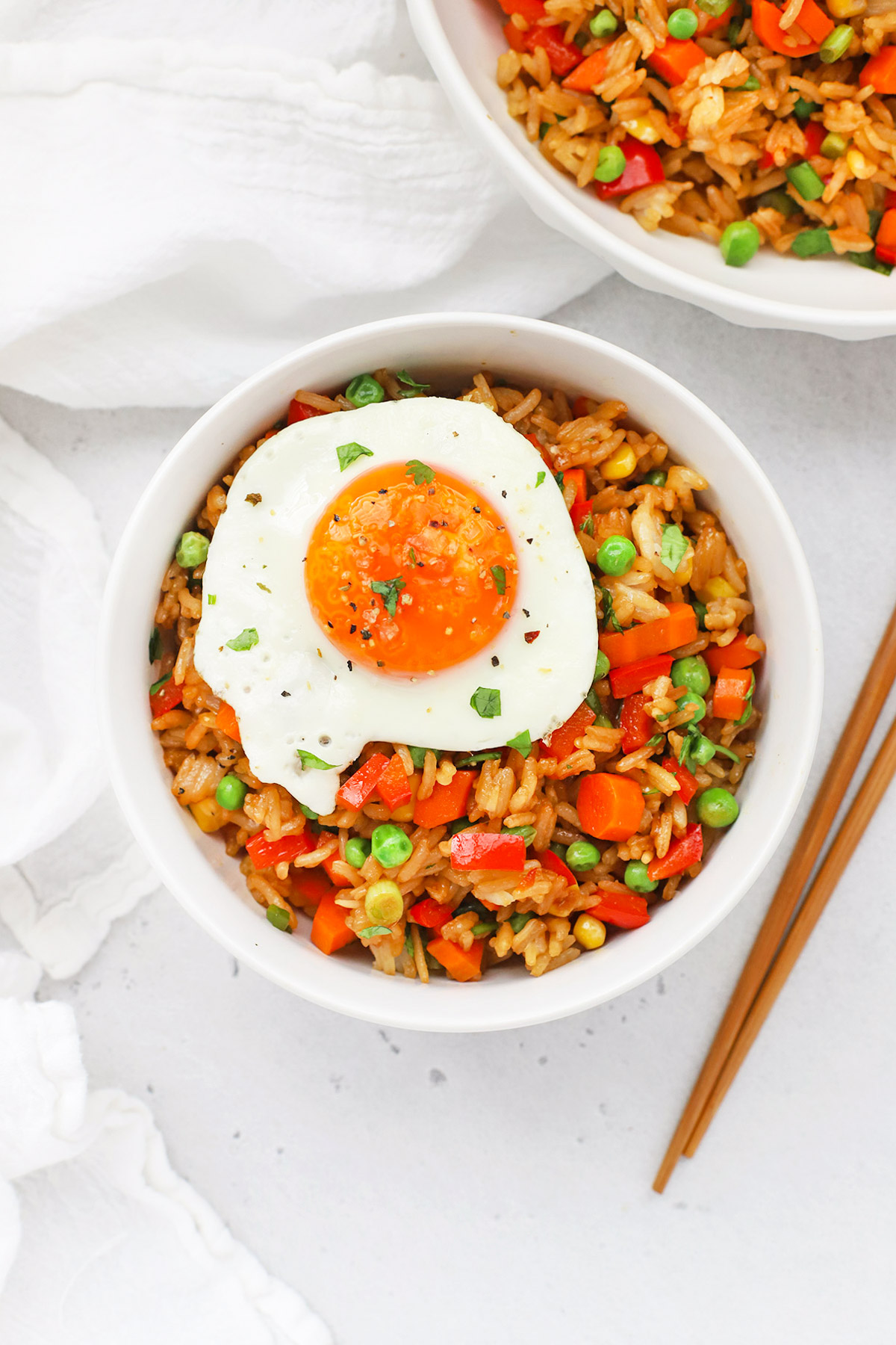 Overhead view of two bowls of healthy vegetarian fried rice topped with a sunny-side up egg