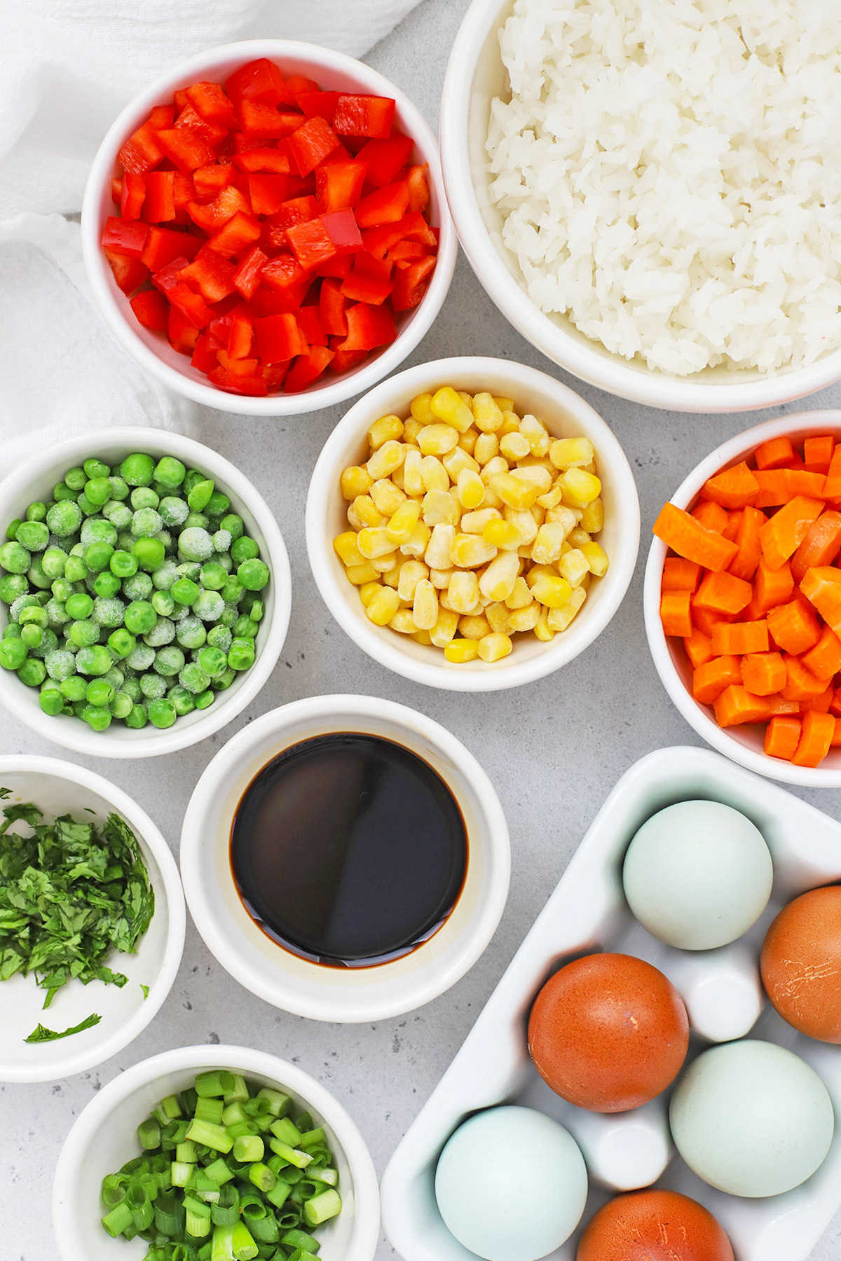 Overhead view of ingredients for healthy vegetarian fried rice in bowls--tamari, colorful veggies, rice, and farm fresh eggs.