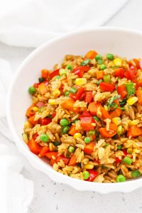 Front view of a serving bowl of healthy vegetarian fried rice with colorful veggies